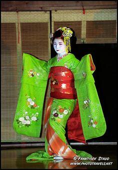 Photograph of Maiko girl (Geisha apprentice) in green kimono dances in Kyoto