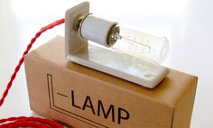"""David Kitz' L-Lamp which """"...showcases the aesthetic qualities of the industrial parts being used: the lightbulb, the cloth cord, the plugs, and the rotary switches"""" which many lights are designed to conceal."""