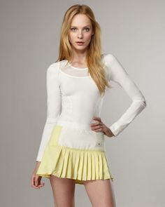 Who's ready for tennis? This candy-colored adidas by Stella McCartney tennis skirt boasts a pastel yellow shade and white front panel to ensure your style doesn't get lost in the cardio shuffle.    White/yellow pleated jersey.  Thin waistband.  Front white panel with logo tag stitched in corner.  Pleated style.  Hem hits mid-thigh.  Pull-on waist.  Polyester.  Imported