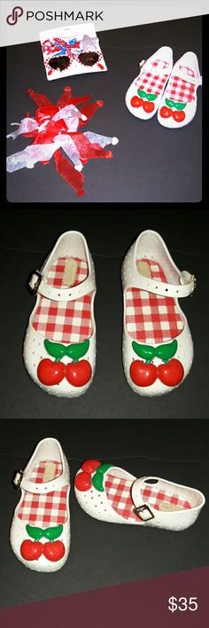 Mini Melissa strawberry topped jellies White jellies with adorable cherries on the front ... a white and red gingham footbed..with the classic Mini Melissa delicious scent...velcro strap closurer...were worn once for a walk around the block.. before I decided they were too small... there is a little flaws that could probably easily be fixed with a magic eraser...or any Scuff cleaner...flaws in pic #7...flaw is not visible when wearing...besides that they still are PERFECT  and have plenty of…