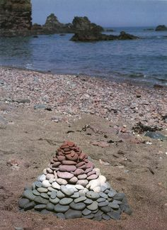 Scotland - environmental art by Andy Goldsworthy. Pile of multicoloured stacked in the form of a pyramid at the beachside
