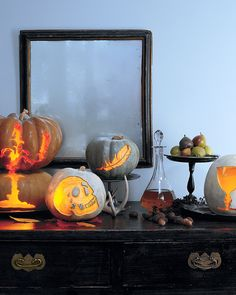 This sideboard tableau intersperses luminous pumpkins with a decanter of wine, a stand with fruit, and other objects evocative of Edgar Allan Poe and his tales of horror. T