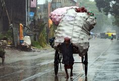 n Indian rickshaw-puller transports goods along a road in heavy rain in Kolkata