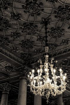 Bold chandelier and black detailed ceiling