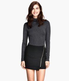 Een top van zacht tricot met lange mouwen en een rolkraag.