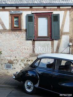 Schwarze DKW 3=6 Limousine mit weißem Dach aus den Fünfziger Jahren vor einem altem Fachwerkhaus