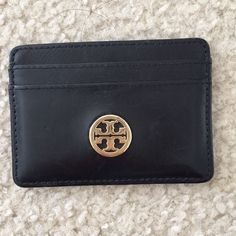 Tory burch dena slim card case black card case that was barely used. just had a few minor scratches on the back from being tossed in my bag. has two card slots on each side as well as a big slot in the middle. perfect accessory to carry for the gym or a target run! Tory Burch Accessories Key & Card Holders