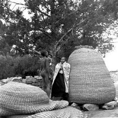 Africa | Sotho woman standing next to an immense basket taller than her. She's looking at a boy standing on a similar sized basket that is laid flat. The Lesotho people weave these baskets to hold-store their corn. Lesotho | ©Constance Stuart Larrabee, 1947