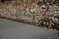 """Tiled memorial wall to the victims of 9/11.  Hand-painted bisque tiles are decorated and have been attached to a wire fence next to """"Our name is Mud"""" in Greenwich, USA."""