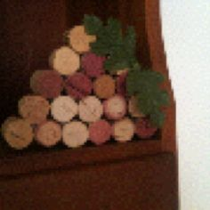 """Found this idea on Pinterest.  I cut used wine corks in half, hot glued together to make wine cork """"grapes"""" to accent my wine bar"""