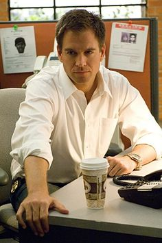 Special Agent Tony DiNozzo, played by Michael Weatherly, of NCIS,  looks serious and, of course, hot. (Characters in older shows had liquor in the desk drawer, now they always drink coffee.)