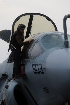 """GULF OF OMAN (July 31, 2013) Aviation Machinist's Mate 3rd Class Andres Mahecha, of San Diego, currently assigned to the """"Gray Wolves"""" of Electronic Attack Squadron (VAQ) 142, cleans the canopy of an EA-6B Prowler on the flight deck of the aircraft carrier USS Nimitz (CVN 68). (U.S. Navy photo by  Devin Wray/Released)"""