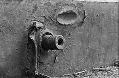 A German artillery shell embedded in the armor of a Soviet KV-1 tank. It probably came from an early model Panzer IV, which mounted the Kampfwagenkanone 37 L/24 75mm tank gun, a low-velocity cannon mainly designed to fire high-explosive shells. The shell's profile matches the Panzergranate 39. It's possible that the impact popped out the base fuse which stopped it from detonating. Note the ricochet mark from a prior hit just above it.