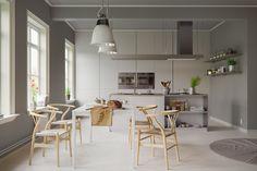 Phòng ăn màu xám này lại được thắp sáng nhờ bộ ghế gỗ Wishbone với những đường cong, một phong cách mang tính biểu tượng của nhà thiết kế đồ nội thất Hans Wegner người Đan Mạch.