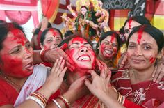 A Hindu woman is smeared with vermillion powder as part of a ritual on the last day of the Durga Puja festival in northern India.