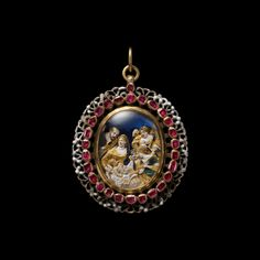 The Birth of Jesus.  Gold and silver oval locket, the front with an outer border of black and white openwork ornament surrounding a line of table-cut rubies enclosing a glass covered cut-out gold enamelled scene of the Nativity, with two angels in the stable adoring the infant Jesus watched by his mother, the Virgin Mary and by St. Joseph set against a blue foil ground.  The back is enamelled with a floral pattern in different colours opening to the inside which is enamelled with an infant…