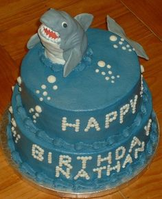 Shark Birthday - Two tiered cake iced in buttercream with buttercream bubbles and writing. The shark is molded out of rice krispy treats and covered in fondant, all the details are fondant except the fins and tail are gumpaste. This cake was for my nephews shark themed birthday party and he loved it! I saw a couple cakes like this where the shark is sort of swimming through the cake on this site, thanks for the inspiration!