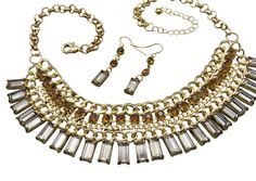 Dare to dazzle with a stunning amber and topaz necklace earring set drenched in gold and large luminous rhinestones.