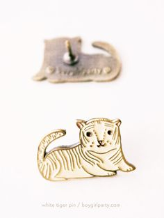 Tiny white tiger pin from the boygirlparty shop: http://shop.boygirlparty.com/collections/_new/products/white-tiger-enamel-pin-brass-lapel-pin