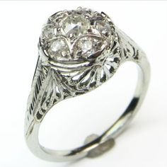 The Clever Cluster: What a neat trick! This lovely and lofty filigree ring takes 7 pretty little antique cut diamonds and holds them close, with beautiful looping filigree highlighted by milgrain and engraving. Ca 1930.  Maloys.com