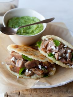 Arepas filled with Carnitas and Guasacaca. Light and crisp corncakes filled with savory carnitas and topped with creamy gauasacaca; a great dish anytime of the day!