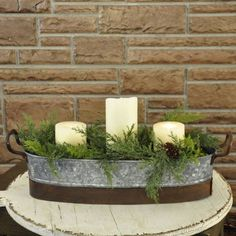 """Create a flower garden wherever you need a bright accent, either inside your home or on a covered porch. Easily change seasonal summer flower pots filled with dahlias or zinnias to an eye-catching display of winter's greens or poinsettias. This striking galvanized planter also creates a country farmhouse centerpiece when filled with faux greens accented with candles or bright ornaments. Handles and metal base strip have the look of rusted iron. Decorative accents are sold separately.21""""…"""