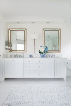 """Two Uttermost Palais Beaded 30"""" x 40"""" Gold Wall Mirrors are mounted to a white wall beneath recessed lighting and above a white dual washstand fitted with polished nickel knobs and a white quartz countertop holding polished nickel faucets in front of a marble hex backsplash lit by a French brass wall sconce."""