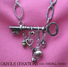 "KeY 2 HaPPiNeSS CHaRMeD NeCkLaCe, ""Love is the master key that opens the gates of happiness"" A vintage skeleton key suspended from bits & pieces of several unusual chain links creates a unique necklace with silvertone hearts, czech glass & African silver bead charms, vintage rhinestone button, & grey crystal bead dangling from the key, which has a lovely antique silver patina & surely holds the ""key 2 happiness."", Jewelry Project"