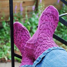 Worked from the cuff down, these socks use twisted and wrapped stitches to evoke the elegant curves of a fence or gate made of wrought iron. When combined with yarn in a cheerful purple or pink, this brings to mind the vivid shades of a garden at its fullest bloom. These socks are a perfect small project for summer, but if you can't knit these up under the sun, make them in winter as a reminder that warmer weather will come again!