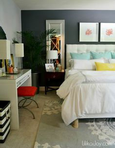 Nuetral bold feature wall in dark grey. Pops of bright colour in accessories, chair, pillows etc