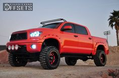 Orange toyota tundra lifted 4x4 with offset rims and LED lighting.