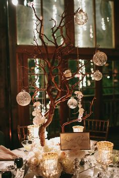 Love the natural branches with decorations hanging. I like adding hanging tea lights mixed with the glass balls.