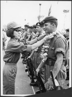 New Zealand soldier presented with a garland of flowers. Saigon [Ho Chi Minh City], Vietnam, c.1965.