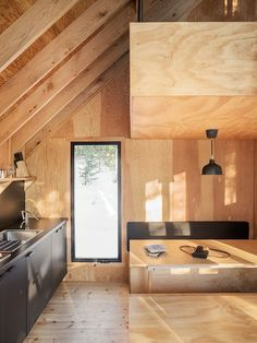 The interior space comprises a single volume, with a kitchenette, living area, and dining table on the ground level, and a sleeping loft perched above that is suspended by steel rods. Montreal Architecture, Modern Architecture, La Pointe, Cabinet D Architecture, Shelter Design, Journal Du Design, Refuge, A Frame Cabin, Sleeping Loft