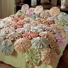 Un couvre-lit recouvert de yoyos en tissu fleuri /: bed cover, tissu, flowers