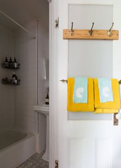 The bathroom entrance pops with goldenrod and turquoise towels.