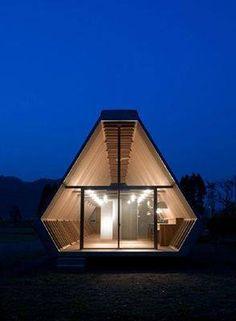 """Onigiri House: Un proyecto relacionado con un """"aperitivo japonés""""  Con su forma triangular-tubo y casco de madera, el innovador diseño está lleno de luz natural a través de ventanas que recubren la parte superior y las base de las paredes con una luz al final de largo túnel de madera."""