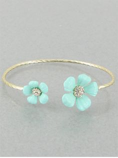 Beautifully designed delicate thin gold bracelet with two mint flowers on each end. A sparkling rhinestone in the center of each flower.  Adjustable to fit women of all wrist sizes.