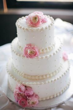 Simple tiered cake with flowers, dots and decorative border