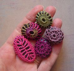 I love the contrast of the bright  crochet threads and the smooth, dark pebbles.