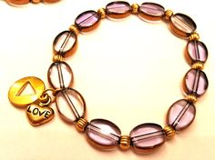These clear purple Czech glass beads are really popular. Edged with gold, theyre surprisingly versatile. Shown with gold-tone metal spacers and strung on a sturdy latex-free PowerCord elastic band.  This bracelet features a gold-tone silhouette-style AA charm (14mm) with either a Love heart charm or a gold-tone key charm.  Please ask about customization. Other charms can be substituted, or the bracelet can be sold with no charm (price may vary).