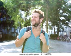 Close up portrait of a happy young man traveling with backpack and earphones