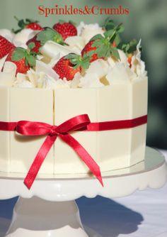 White chocolate mud cake with chocolate panels, chocolate curls, white chocolate truffles and fresh strawberries.