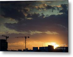 Construction cranes shilouettes and rooftops in a warm sunset cloudscape photography.