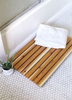 White Bathroom With Honeycomb Tile Flooring Containing Wooden Bath Mat Potted Aloe Vera Also
