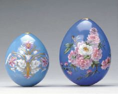 TWO RUSSIAN PORCELAIN EGGS, 20TH CENTURY. The first decorated and gilt with a formal scrolling bouquet in puce and white on a pale blue ground; the second with white narcissus and prime rose on a cobalt ground, both pierced at each end.