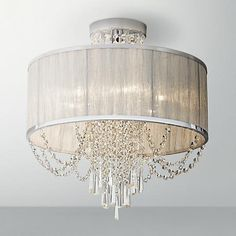 This silver organza shade and chrome ceiling light features clear crystal bead that radiate when illuminated.