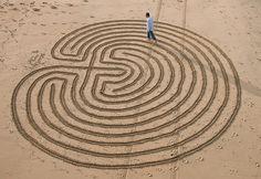 A sand labyrinth artist walking his own path