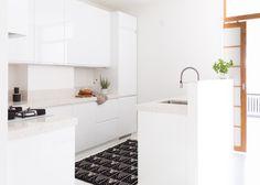 KVARTSIKOMPOSIITTI JA VALKOINEN VETIMETÖN OVI  Tämä moderni töölöläiskoti remontoitiin täysin. Keskellä asuntoa sijaitseva keittiö on valkoisten kiiltävien ovien ja vaaleiden kvartsitasojen ansiosta avara ja valoista. Tiskiallas on poikkeuksellisesti saarekkeessa, mutta fiksu seinäke kätkee tiskit ja ruoanlaiton jäljet.   Lieden päällä on valkoinen Noppa-liesituuletin ja tasoon on integroitu valkoinen, lasinen Lofra-kaasukeittolevy. Integroitu sähköuuni on Siemensiltä.