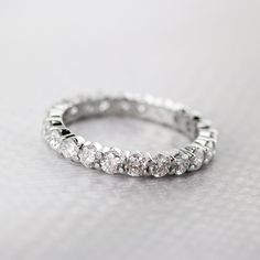 Pre-Owned Ladies Diamond Enternity Band crafted in platinum and graced with 22, gorgeous round full cuts with a colletive carat weight of 1.50 carats, an average color of G to H, and an average clarity of VS1-VS2. Band is in excellent condition and is a size 6.25.